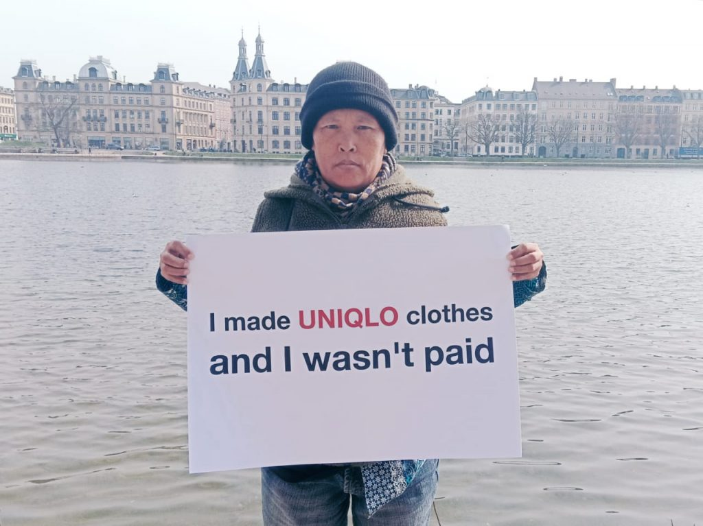 Living wage myth | Person holding sign that ays: I made Uniqlo clothes and I wasn't paid