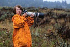 Patagonia boy in adult jacket holding huge camera